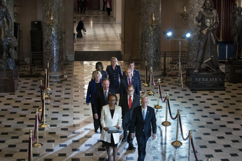 Clerk of the House Cheryl Johnson, left, and House Sergeant at Arms Paul Irving pass through Statuary Hall at the Capitol to deliver the articles of impeachment against President Donald Trump to the Senate, on Capitol Hill in Washington, Wednesday, Jan. 15, 2020. Following are impeachment managers, House Intelligence Committee Chairman Adam Schiff, D-Calif., left, and House Judiciary Committee Chairman Jerrold Nadler, D-N.Y., and other managers Rep. Hakeem Jeffries, D-N.Y., Rep. Sylvia Garcia, D-Texas, Rep. Val Demings, D-Fla., Rep. Zoe Lofgren, D-Calif., and Rep. Jason Crow, D-Colo. (AP Photo/J. Scott Applewhite)