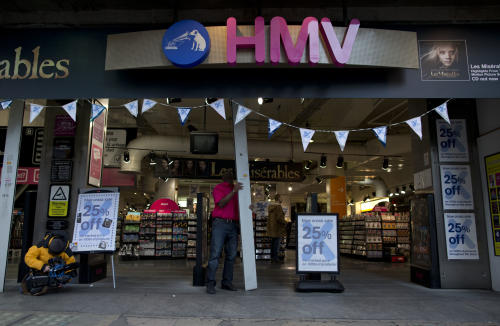 A worker opens a branch of HMV at the start of the day on Oxford Street in London, Tuesday, Jan. 15, 2013. British music and entertainment retailer HMV admitted defeat on Tuesday after more than 90 years on the U.K high street, suspending trading in its shares and calling in administrators to try to salvage any viable parts of the business. HMV is the last big retail chain selling recorded music in Britain and employs more than 4,000 people working in 238 stores, which will remain open for the time being. The company's management confirmed that it had failed to gain agreements with lenders and suppliers to continue trading. (AP Photo/Matt Dunham)