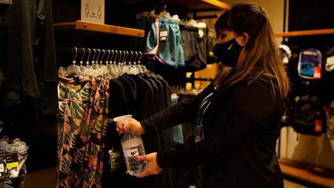 Pekerja menyemprotkan disinfektan pada pakaian di salah satu toko di Abasto Shopping Mall di Buenos Aires, Argentina, Rabu (14/10/2020). Setelah tujuh bulan ditutup, pusat perbelanjaan Buenos Aires dibuka kembali saat lonjakan kasus terjadi di pedalaman negara itu. (AP Photo/Victor R. Caivano)