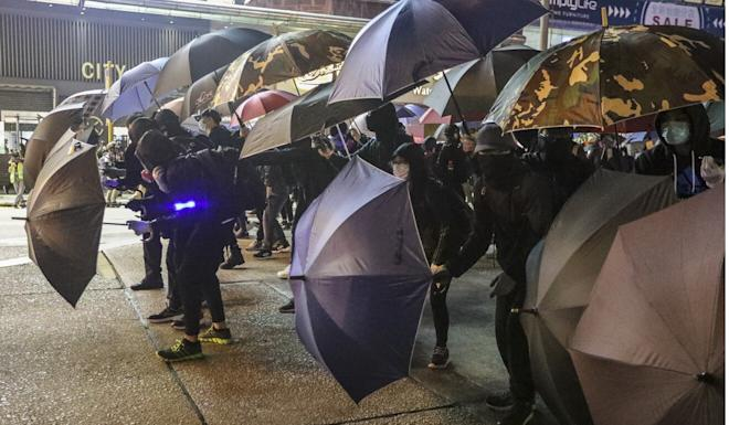 Protesters in Hong Kong use umbrellas for cover during a protest in Mong Kok. Photo: Felix Wong