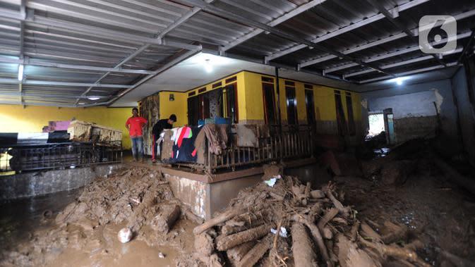 Warga membersihkan rumah usai banjir bandang melanda Kampung Cibuntu, Desa Pasawahan, Kecamatan Cicurug, Sukabumi, Jawa Barat, Selasa (22/9/2020). Data sementara puluhan bangunan rusak berat, 12 rumah hanyut, dan dua korban hilang masih dicari. (merdeka.com/Arie Basuki)