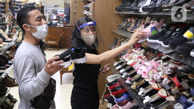 Calon pembeli memilih sepatu di salah satu pertokoan di Pasar Baru, Jakarta Pusat, Selasa (9/6/2020). Pusat perbelanjaan tersebut kembali dibuka, meski masih dalam masa Pembatasan Sosial Berskala Besar (PSBB) transisi. (Liputan6.com/Angga Yuniar)