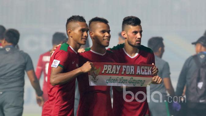 Abduh Lestaluhu, Manahati Lestusen, Stefano Lilipaly memegang spanduk Pray For Aceh usai laga melawan Thailand pada Final Piala AFF 2016 di Stadion Pakansari, Bogor, (14/12/2016). (Bola.com/Nicklas Hanoatubun)