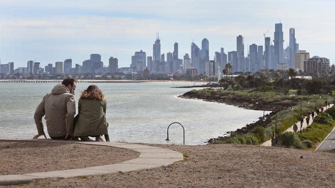 Suami istri beristirahat dari berolahraga dengan pemandangan cakrawala Melbourne (11/8/2020). Negara bagian Victoria melaporkan 19 kematian akibat virus corona pada 11 Agustus, menjadikannya hari yang sama mematikan bagi pandemi di negara itu meskipun jumlah kasus baru turun. (AFP/William West)