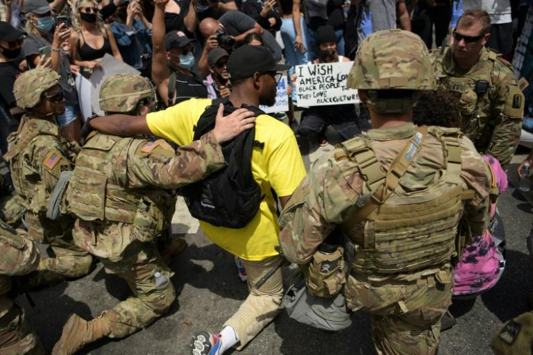 Protesters and members of the Army National Guard kneel together in Los Angeles on June 2, 2020 during a demonstration over the killing of George Floyd
