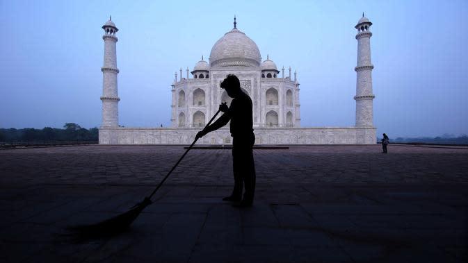 Seorang pria menyapu monumen Taj Mahal di Agra, India, Senin (21/9/2020). Taj Mahal dibuka kembali Senin setelah ditutup selama lebih dari enam bulan karena pandemi virus corona. (AP Photo/Pawan Sharma)