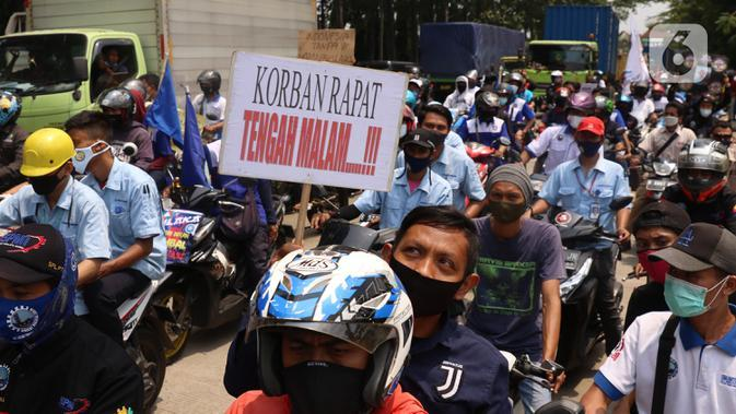 Buruh membawa spanduk saat konvoi di Kota Tangerang, Banten, Selasa (6/10/2020). Dalam aksi tersebut mereka menolak UU Omnibus Law Cipta Kerja yang sudah disahkan oleh DPR RI. (Liputan6.com/Angga Yuniar)