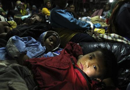 A child refugee lies down at temporary shelter as a safety precaution after Sinabung volcano erupted at Tiganderket village in Karo district, Indonesia's north Sumatra province