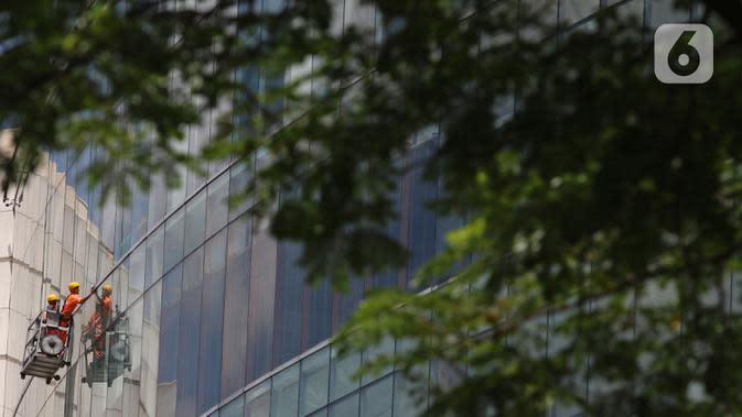 Pekerja membersihkan kaca gedung bertingkat di Jakarta, Kamis (2/4/2020). Keluarnya Peraturan Pemerintah (PP) Nomor 82 Tahun 2019 yang resmi berlaku pada 2 Desember 2019 diharapkan dapat meningkatkan jumlah perusahaan dan pekerja peserta skema BP Jamsostek. (Liputan6.com/Herman Zakharia)