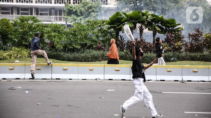 Seorang perempuan berlari di tengah massa pendemo yang terlibat bentrok dengan polisi di kawasan Patung Kuda, Jakarta, Selasa (13/10/2020). Perempuan yang terjebak itu diselamatkan pendemo saat unjuk rasa menolak Omnibus Law Undang-Undang Cipta Kerja tersebut ricuh. (Liputan6.com/Faizal Fanani)