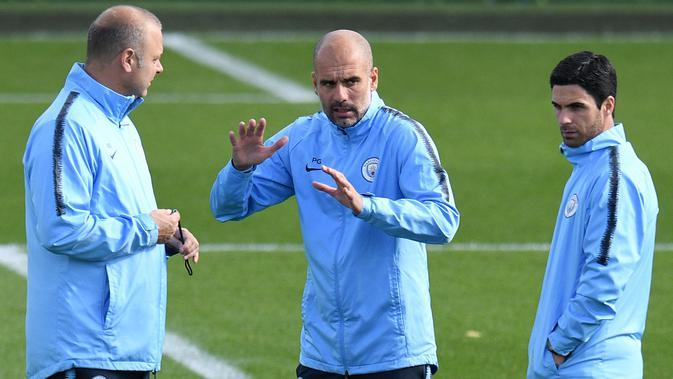 Mikel Arteta berdiskusi dengan Pep Guardiola. (AFP Photo/Oli Scarff)