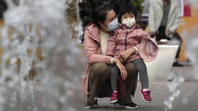 Seorang wanita dan seorang anak mengenakan masker untuk mengekang penyebaran COVID-19 di Beijing, China, Minggu (11/10/2020). Meski penyebaran COVID-19 hampir diberantas di China, pandemi masih melonjak di seluruh dunia dengan jumlah kematian yang terus meningkat. (AP Photo/Andy Wong)