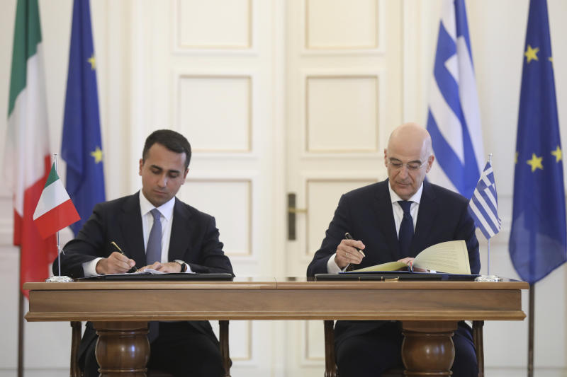 Greek Foreign Minister Nikos Dendias, right, and his Italian counterpart Luigi Di Maio asign an agreement following their meeting , in Athens, on Tuesday, June 9, 2020. Greece will lift all restrictions on Italian tourists entering the country gradually between June 15 and the end of the month, Greece's foreign minister said Tuesday.(Costas Baltas /Pool via AP)