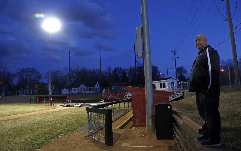 Activities director Dave Boie, right, looks out over the lit baseball field at Richfield High School Wednesday night, April 8, 2020 in Richfield, Minn. Seeking to brighten spirits amid the virus outbreak, the symbolic act of turning on the lights became a movement — fueled by social media with the hashtag #BeTheLight — across the country. (AP Photo/Jim Mone)