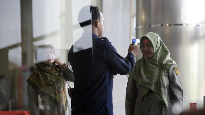 Petugas mengecek suhu tamu dan pegawai yang akan masuk ke Loby di Gedung KPK, Jakarta, Kamis, (12/3/2020). KPK menerapkan pengecekan suhu tubuh tersebut untuk mengantisipasi penyebaran virus corona atau covid-19. (merdeka.com/Dwi Narwoko)