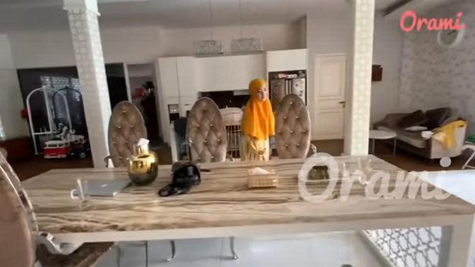April juga memperlihatkan ruang makan keluarganya yang tidak jauh dari belakang sofa tadi. Disamping meja juga ada dapur kering yang bisa digunakan untuk buat makanan ringan. (Youtube/Orami Indonesia)