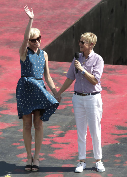 U.S. talk show host Ellen DeGeneres, right, introduces her wife Portia de Rossi during the recording of DeGeneres' show in Sydney, Australia, Saturday, March 23, 2013. (AP Photo/Rick Rycroft)
