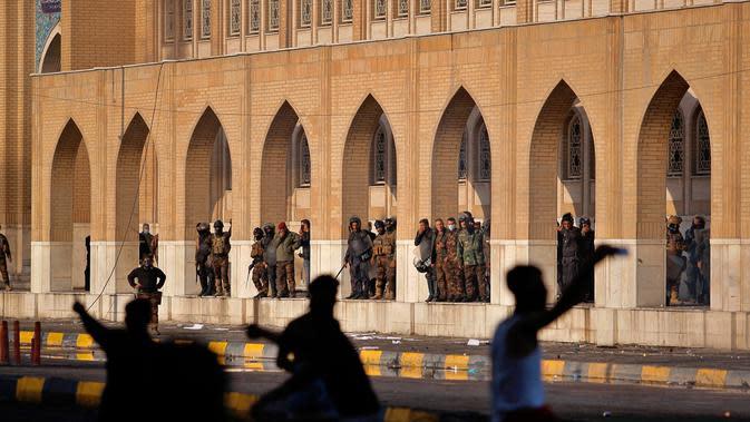 Pasukan keamanan berusaha membubarkan demonstran antipemerintah selama bentrokan di Najaf, Irak, Kamis (28/11/2019). Kerusuhan di Ibu Kota dan wilayah selatan Irak terus meningkat setelah pembakaran gedung Konsulat Iran. (AP Photo/Anmar Khalil)