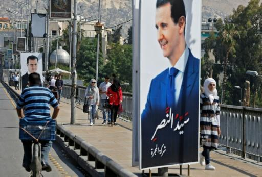 People walk near a portrait of Syrian President Bashar al-Assad hanging in a street in the Syrian capital Damascus on May 31, 2018