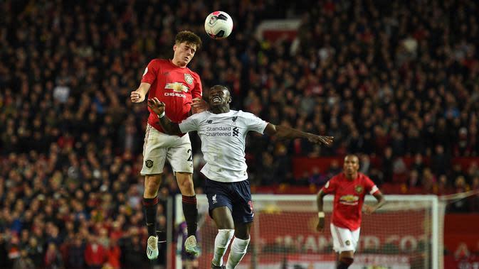 Gelandang Manchester United, Daniel James, duel udara dengan striker Liverpool, Sadio Mane, pada laga Premier League di Stadion Old Trafford, Manchester, Minggu (20/10). Kedua klub bermain imbang 1-1. (AFP/Oli Scarff)