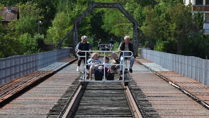Sejumlah orang menyeberangi Viaduc des Fades dengan menaiki velorail di jalur kereta api tua Les Ancizes-Comps, Prancis, Selasa (18/8/2020). (FILIPPE DESMAZES/AFP)