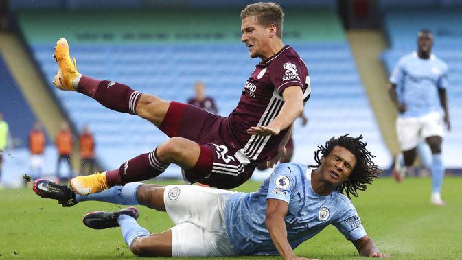 Bek Manchester City, Nathan Ake, menjatuhkan pemain Leicester City, Dennis Praet, pada laga Liga Inggris di Stadion Etihad, Senin (28/9/2020). City takluk 2-5 dari Leicester. (Catherine Ivill/Pool via AP)