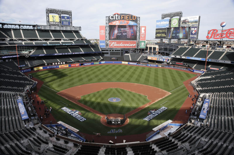 FILE - In this Oct. 29, 2015, file photo, members of the media and grounds crew work on the field at Citi Field in New York, the day before Game 3 of the World Series between the Mets and the Kansas City Royals at the stadium. Baseball Commissioner Rob Manfred says talks have ended over the proposed sale of a controlling share of the Mets from the families of Fred Wilpon and Saul Katz to hedge fund manager Steven Cohen. (AP Photo/Peter Morgan, File)