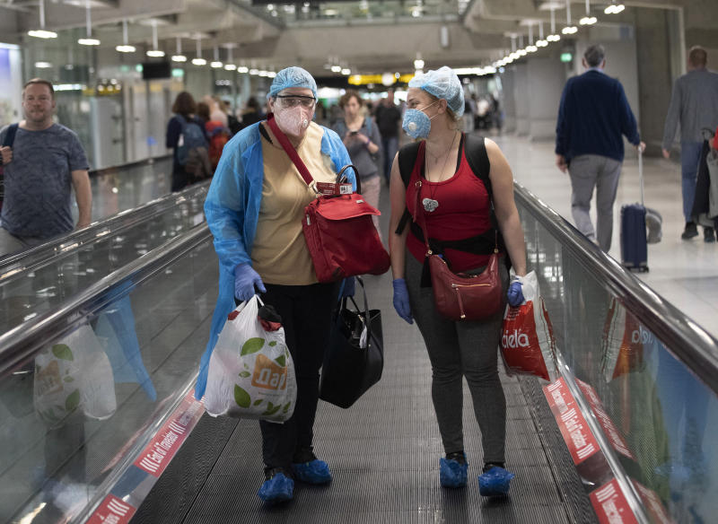 Tourists wearing protective gear against the Covid-19 virus arrive at the Suvarnabhumi Airport  in Bangkok, Thailand, Wednesday, March 4, 2020. (AP Photo/Sakchai Lalit)