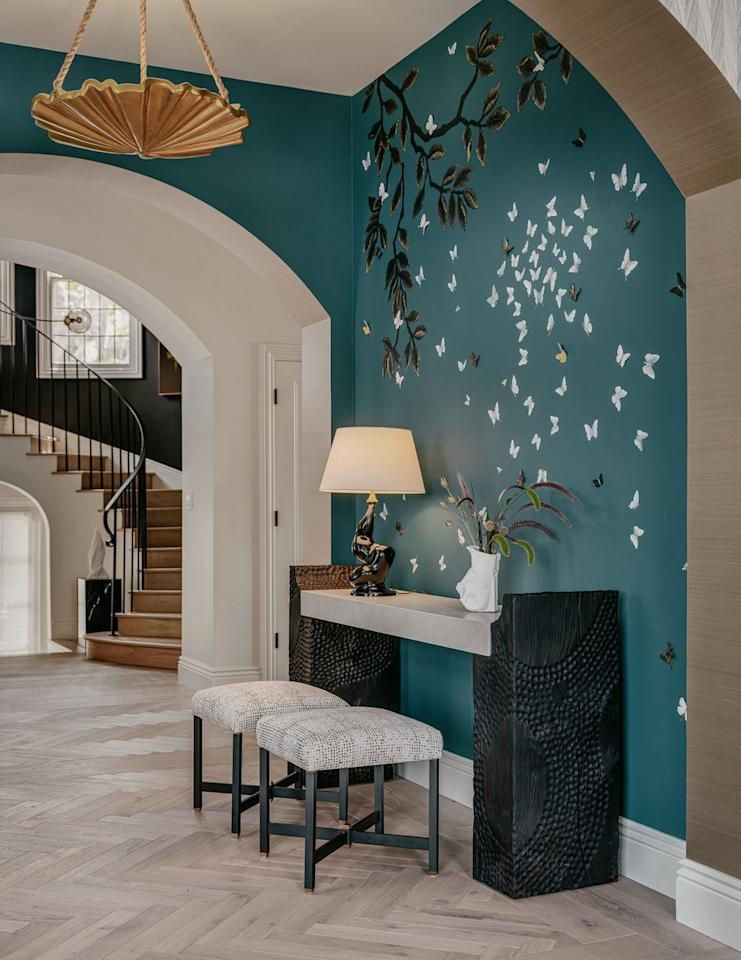 """<p>In the foyer, the team at <a href=""""https://www.leapinteriors.com/mobile/"""" target=""""_blank"""">Leap Interior Design</a> was inspired by a study called """"Nature Always Wins,"""" which highlights the dichotomy between the strength and the fragility of our natural world. Every piece in this space was designed or made in California, in order to minimize the environmental footprint. The console table was hand-carved by <a href=""""https://www.instagram.com/aderynstudio/?hl=en"""" target=""""_blank"""">Aderyn Studio</a>, founded by Chelsea Brown of Leap Interior Design and her husband, Phil Vaughn.</p>"""