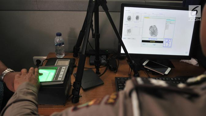 Petugas melakukan perekaman sidik jari warga saat pembuatan Smart SIM (Surat Izin Mengemudi) di Jakarta, Minggu (22/9/2019). Smart SIM mempunyai fungsi menyimpan data diri pemilik SIM, mencatat data historikal pelanggaran lalu lintas, dan sebagai uang elektronik. (merdeka.com/Iqbal S Nugroho)
