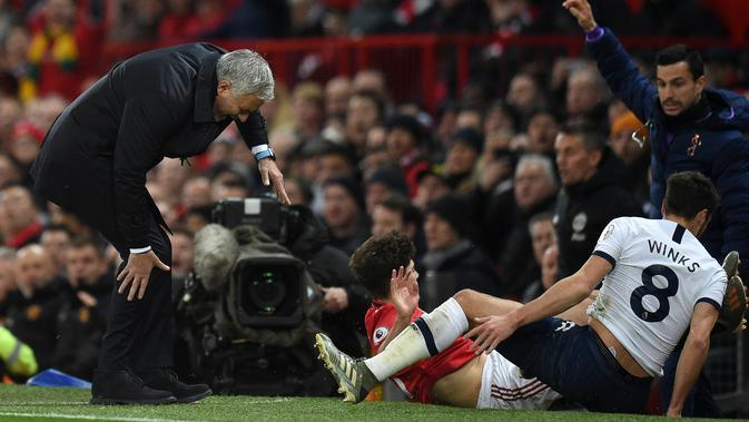 Pelatih Jose Mourinho kesakitan saat tertendang pemain Tottenham Hotspur, Harry Winks dan pemain Manchester United, Daniel James pada pertandingan lanjutan Liga Inggris di Old Trafford, Rabu (4/12/2019). Tottenham kalah tipis atas MU 2-1. (AFP Photo/Oli Scarff)