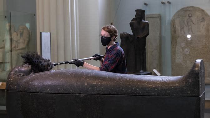 Seorang staf membersihkan debu pada permukaan sebuah benda pameran saat pratinjau media menjelang pembukaan kembali Museum Inggris di London, Inggris (25/8/2020). Museum tersebut akan dibuka kembali pada 27 Agustus. (Xinhua/Han Yan)