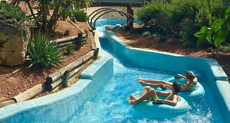 Two people in tyres go down a waterslide at Adventure World in Perth.