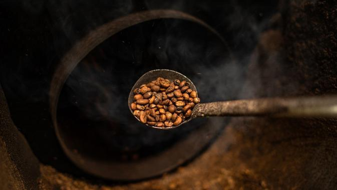 Pekerja memeriksa biji kopi panggang di Pabrik Kopi Antong, Taiping, Perak, Malaysia, 28 September 2020. Pabrik Kopi Antong menggunakan mesin antik dan metode pemanggangan tradisional untuk menghasilkan bubuk sarat kafein yang terkenal selama 87 tahun. (Mohd RASFAN/AFP)