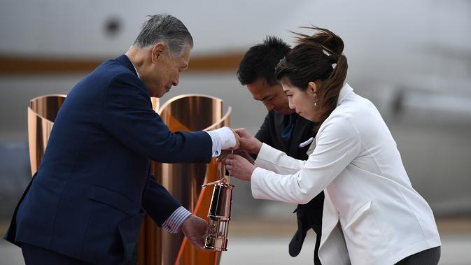 Presiden Olimpiade Tokyo 2020, Yoshiro Mori, menerima api Olimpiade saat tiba dari Yunani di Pangkalan Udara Matsushima, Jepang, Jumat (20/3). Di tengah pandemi virus corona Covid-19, prosesi menuju Olimpiade Tokyo 2020. (AFP/Philip Fong)