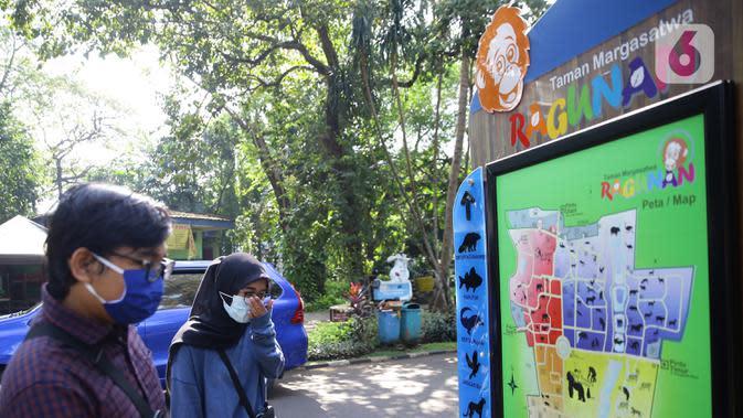 Pengunjung melihat denah saat mengunjungi Taman Margasatwa Ragunan, Jakarta, Sabtu (20/6/2020). Ragunan mulai dibuka kembali untuk pengunjung pada Sabtu ini di masa PSBB transisi dengan pembatasan dan penerapan protokol kesehatan yang ketat. (Liputan6.com/Herman Zakharia)