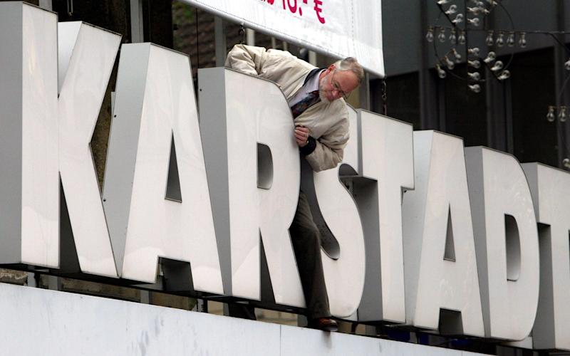 A worker fixes the letters at a Karstadt store in downtown Essen, western Germany, Tuesday Sept. 28, 2004. Struggling German retailer KarstadtQuelle said Tuesday it plans to sell 77 of its department stores as soon as possible as it responds to slumping sales in economically lagging Germany. KarstadtQuelle announced Monday that it will undergo a 1.4 billion (US$1.72 billion) restructuring plan to refocus the group on its core operations, with German media speculating that the company was planning massive lay-offs and a capital increase. (AP Photo/Frank Augstein) - FRANK AUGSTEIN/AP