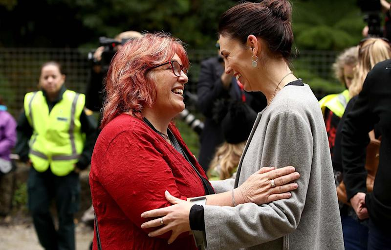 A diamond ring is seen on the middle finger of Jacinda Ardern's hand (right) as she embraces Anna Osborne from the Family Reference Group, at a ceremony at Pike River. Source: Phil Walter/Getty Images
