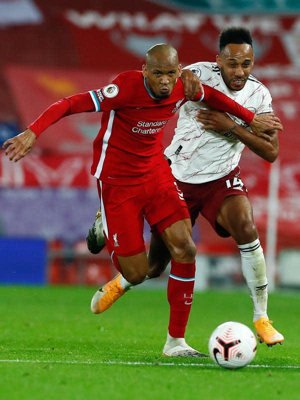 Gelandang Liverpool, Fabinho berebut bola dengan penyerang Arsenal, Pierre-Emerick Aubameyang pada pekan ketiga Liga Inggris di Anfield, Selasa dinihari WIB (29/9/2020). Tertinggal lebih dulu, Liverpool mampu membungkam Arsenal dengan skor 3-1. (Jason Cairnduff / Pool via AP)