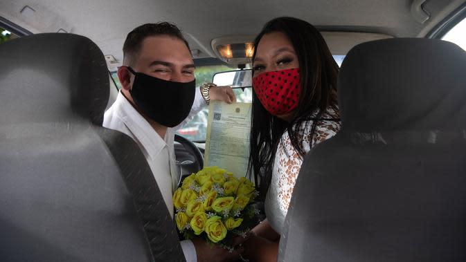 Ayrton (kiri) dan Natasha dengan mengenakan masker berpose setelah pernikahan drive-thru mereka di kantor pencatatan sipil di Santa Cruz, Rio de Janeiro, Brasil, 28 Mei 2020. Fasilitas ini untuk memudahkan pasangan yang ingin mengesahkan hubungan saat pandemi covid-19. (AP/Silvia Izquierdo)