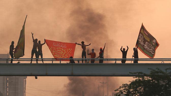 Pengunjuk rasa antipemerintah meneriakkan slogan-slogan selama protes di Baghdad, Irak, Rabu (2/10/2019). Para pejabat Irak mengatakan beberapa pengunjuk rasa tewas dan sejumlah lainnya terluka di tengah baku tembak dan bentrokan di Baghdad. (AP Photo/Hadi Mizban)
