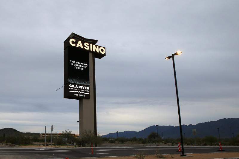 A sign shows the Gila River Hotels & Casinos Vee Quiva location closed due to the coronavirus Friday, March 20, 2020, in Laveen, Ariz. Native American tribes across the U.S. have been closing their properties, with all casinos in the Phoenix metro area closing down. (AP Photo/Ross D. Franklin)