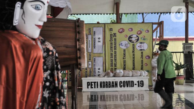 Pekerja melintas di depan boneka pocong dan peti mati di Kantor Kecamatan Senen, Jakarta, Kamis (13/8/2020). Pemkot Jakpus menyiapkan peti mati dan boneka pocong di setiap kecamatan sebagai peringatan bahaya Covid-19 dan imbauan untuk tidak mengabaikan protokol kesehatan. (merdeka.com/Iqbal Nugroho)