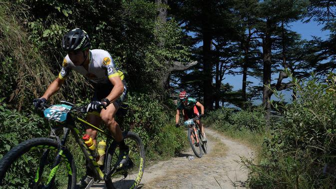Adria Noguera Soldevila dari Spanyol (kiri) bersaing dalam lomba sepeda gunung Himalaya MTB di dekat Mandi, Himachal Pradesh, India utara (4/10). Lomba ini dimulai di Shimla 29 September dan selesai 7 Oktober di Dharamshala. (AFP Photo/Sajjad Hussain)