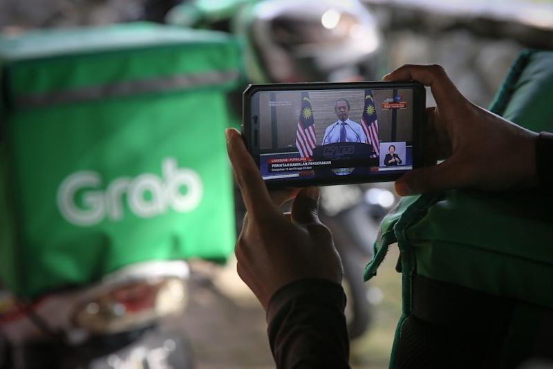 Food delivery rider watching the live telecast of Prime Minister Tan Sri Muhyiddin Yassin's announcement of a movement control order extension due to the Covid-19 pandemic in Shah Alam April 10, 2020. — Picture by Yusof Mat Isa