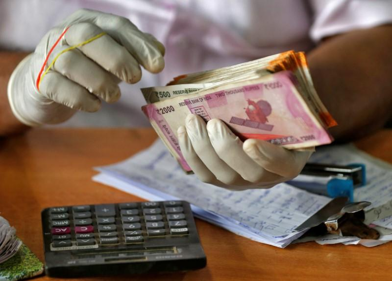 A trader wearing protective hand gloves count Indian currency notes at a market during a 21-day nationwide lockdown to limit the spreading of coronavirus disease (COVID-19) in Kochi