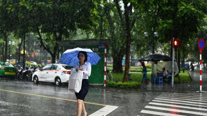 Seorang wanita melintasi jalan saat hujan lebat di Hanoi (14/10/2020). Badai tropis Nangka menghantam Vietnam tengah-utara yang mengakibatkan bencana alam, terutama hujan lebat dan banjir, telah menyebabkan 28 orang tewas dan 12 lainnya hilang. (AFP Photo/Manan Vatsyayana)
