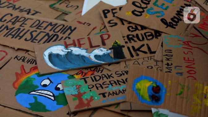 Sejumlah kardus bertuliskan pesan dan gambar ditunjukkan saat aktivis lingkungan hidup dari berbagai LSM berjalan kaki menuju Taman Aspirasi di Istana Merdeka, Jakarta, Jumat (29/11/2019). Aktivis meminta pemerintah segera mendeklarasikan perubahan iklim yang semakin kritis. (merdeka.com/ImamBuhori)