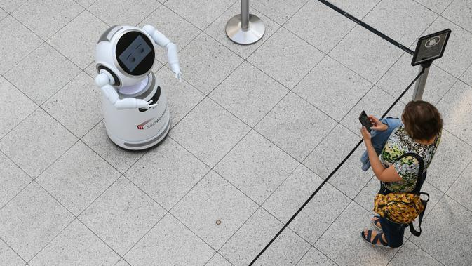 Seorang perempuan mengamati sebuah robot pintar yang menjelaskan tentang langkah pencegahan COVID-19 di sebuah pusat perbelanjaan di Frankfurt, Jerman, pada 12 September 2020. (Xinhua/Lu Yang)