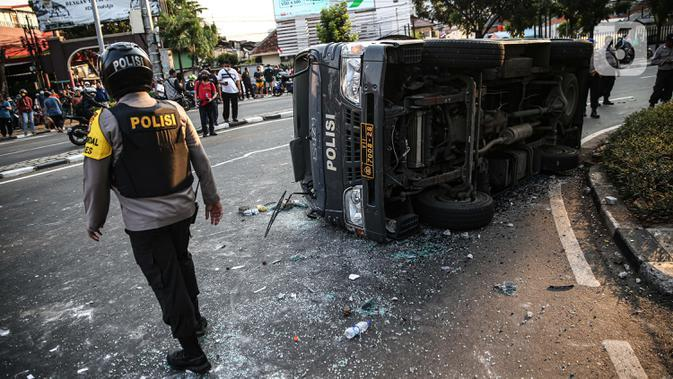 Polisi berjalan dekat sebuah mobil polisi yang dirusak massa saat bentrok di kawasan Pejompongan, Jakarta, Rabu (7/10/2020). (Liputan6.com/Faizal Fanani)